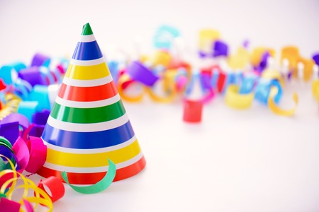 party popper: It is a special day. Image of a bright party hat surrounded by multi colored confetti and popper isolated on white background with copy space