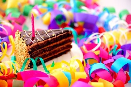 Verjaardagstaart. Close-up bovenaanzicht van een stuk chocoladetaart met een verjaardagskaars versierd met confetti geïsoleerd in witte achtergrond