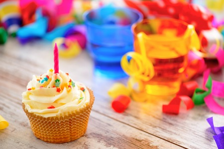 party food: Celebrating a special day. Side view image of a cupcake with multicolored confetti as a frame and bright glasses on the background Stock Photo