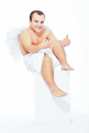 It is love not me. Portrait of an adorable little cupid sitting on the pedestal and smiling at camera pointing at himself isolated on white with copy space photo
