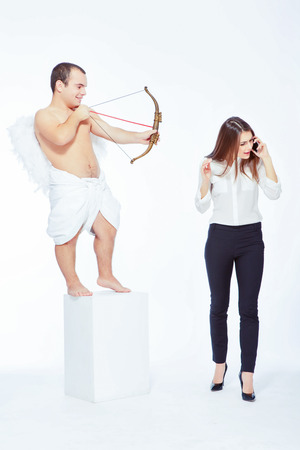 Business vs love. Portrait of an adorable little cupid with a bow taking in sight a young beautiful businesswoman taking over the cell phone isolated on white with copy space Stock Photo