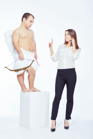 Business vs love. Portrait of an adorable little cupid with a bow failing to strike with love arrow a young beautiful business woman with love arrow isolated on white with copy space photo