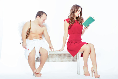 Happy Valentines day. Portrait of an adorable little cupid sitting on the bench with a beautiful woman reading a book isolated on white with copy space