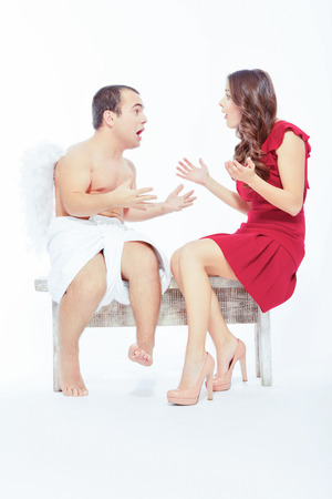 Love failure. Portrait of an adorable little cupid sitting on the bench and arguing with a beautiful unhappy woman isolated on white with copy space