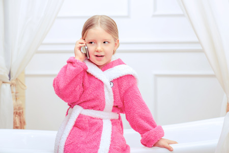 female in douche: Busy princess life. Closeup image of a cute little girl in a pink bathrobe talking over the telephone while sitting on a luxurious bathtub