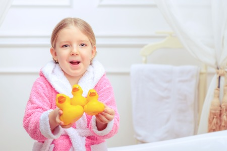 female in douche: Bathtime is fun. Closeup image of a cute little girl in a pink bathrobe holding rubber ducks while sitting on a luxurious bathtub with happy face expression Stock Photo