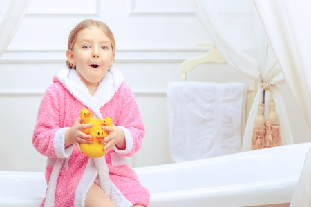 bathtime: Bathtime is fun. Closeup image of a cute little girl in a pink bathrobe holding rubber ducks while sitting on a luxurious bathtub with happy face expression Stock Photo