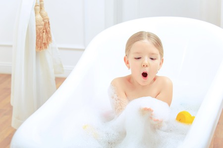 little girl bath: Bath time is fun. Top view image of a cute little girl taking a bath and blowing soap foam while sitting on a luxurious bathtub with rubber ducks