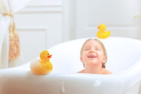 Fürdő idő fun. Szelektív összpontosít kép egy aranyos kislány fürdik és játszik gumi kacsa ülve egy luxus kád