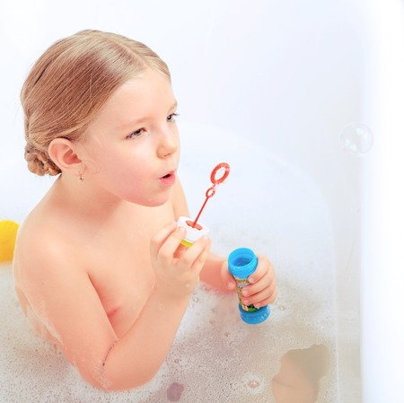 bubble bath: Happy days of childhood. Top view image of a cute little girl taking a bath and playing with soap bubbles while sitting in a luxurious bathtub