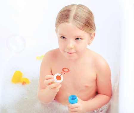 little girl bath: Happy days of childhood. Top view image of a cute little girl taking a bath and playing with soap bubbles while sitting in a luxurious bathtub