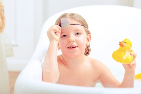 female in douche: Happy days of childhood. Top view image of a cute little girl in sleep mask taking a bath and playing with rubber ducks while sitting in a luxurious bathtub Stock Photo