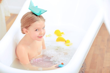 female in douche: Bath time is fun. Top view image of a cute little girl taking a bath with rubber ducks showing paper ship on her head while sitting in a luxurious bathtub