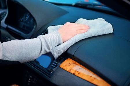 Het schoonmaken van zijn auto. Zijaanzicht close-up van de mannelijke kant het schoonmaken van de auto dashboard met een wisser Stockfoto