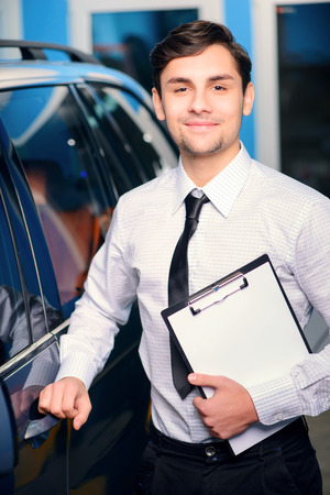 rent car: Helpful and client oriented. Portrait of a handsome smiling car assistance manager in formalwear standing by the luxury car and holding a clipboard with copy space