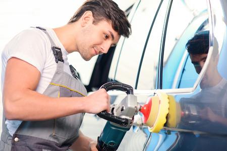 Leidenschaft für Autos. Portrait eines stattlichen lächelnden Automechaniker Polieren der Luxus-Auto mit einer Poliermaschine in Autowerkstatt