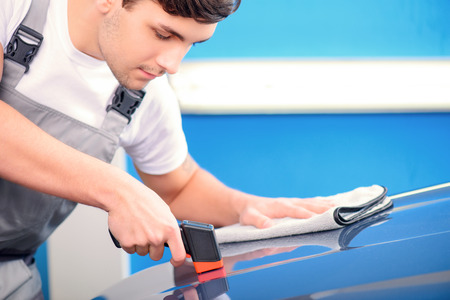 thickness: Measuring coating thickness. Closeup of a handsome car mechanic checking the thickness of car coating with a special electronic tool and cleaning it with wiper in car repair shop