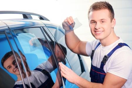 Üdvözöljük autó töltőállomás. Vértes kép egy szép autószerelő kapcsolódó színezés fólia kocsi ablakát, és mosolygós, fényképezőgép speciális töltőállomáson