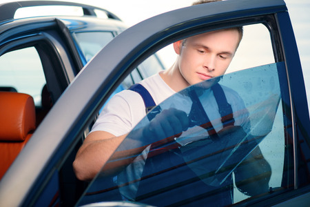 Willkommen zu unserem Auto Tankstelle. Closeup Bild einer schönen Automechaniker Befestigung Tönungsfolie auf Autofenster und Lächeln in die Kamera in spezialisierten Service-Station Lizenzfreie Bilder