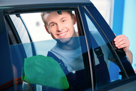 Welcome to our car service station. Closeup image of a handsome car mechanic wiping the car windows with tinting foil and smiling at camera in specialized service station photo