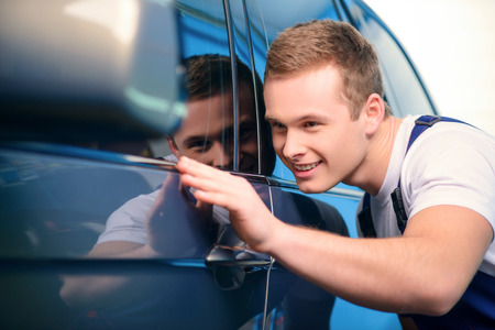 car service station: Welcome to our car service station. Closeup image of a smiling handsome car mechanic wiping the car in specialized service station