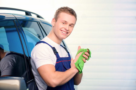 car service station: Welcome to our car service station. Closeup image of a handsome car mechanic wiping hands with a duster and smiling at camera in specialized service station with copy space Stock Photo
