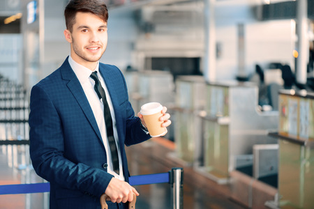 just in time: Just in time for check-in. Handsome young businessman in suit holding a cup of coffee and holding his luggage while standing against airline check in counter in the airport Stock Photo