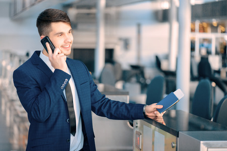 airport check in counter: Business trip. Handsome young businessman in suit holding his passport and talking over his mobile phone while standing against airline check in counter in the airport
