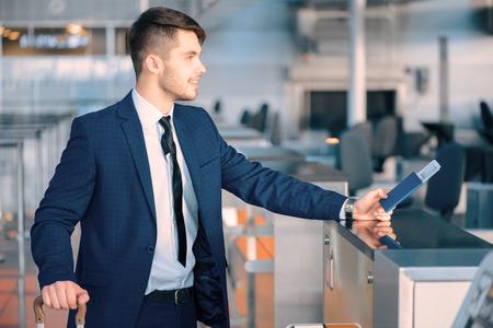 Üzleti út. Oldalnézetből egy csinos, fiatal üzletember öltöny kinyújtotta jegyet állva ellen légitársaság check-in pult a repülőtéren
