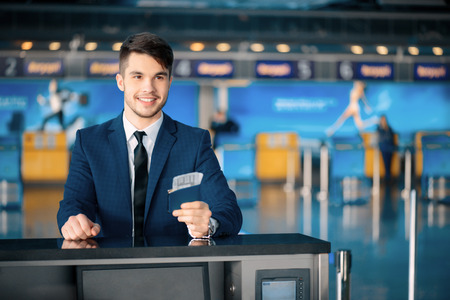 Business travel. Handsome young businessman in suit stretching out his ticket while standing in front of the airline check in counter in the airport