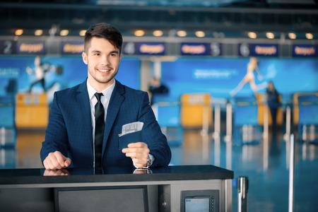 gente aeropuerto: Los viajes de negocios. Empresario joven guapo en traje extendiendo su billete mientras est� de pie en frente del cheque aerol�nea en mostrador en el aeropuerto