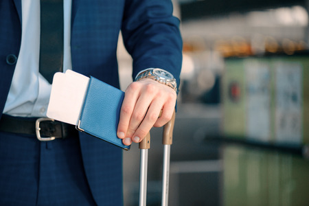 Successful check-in. Cropped image of a handsome young businessman in suit looking at his watch and holding his passport with a ticket while standing in the airport with his luggage Stock Photo