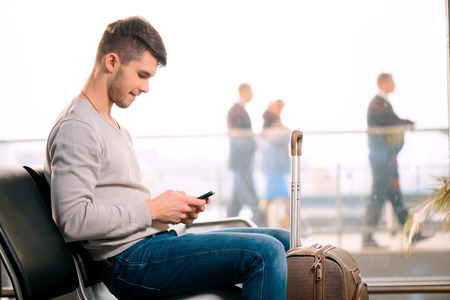 airport window: Texting he is fine. Portrait of handsome smiling man in casual wear holding his luggage and messaging through his mobile phone while sitting in the hall of the airport