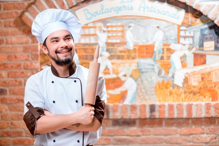 boulangerie: Handsome baker. Handsome young smiling man posing and holding rolling pin in the bakery Stock Photo