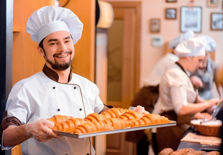 panadero: Panadero conf�a en el trabajo. Panadero joven alegre en delantal que muestra una bandeja de croissants reci�n horneados y sonriendo mientras est� de pie en el fondo de una panader�a