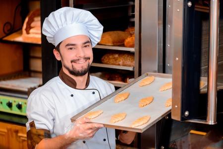 panadero: Panadero Confiados en el trabajo. Panadero joven alegre en delantal poniendo bandeja ga de croissants primas en el horno profesional mientras est� de pie en la tienda de los panaderos Foto de archivo