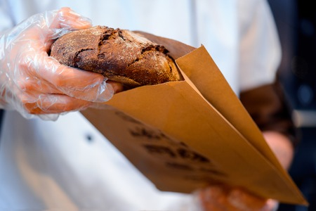 food industry: Fresh baked bread. Cropped image of a fresh baked bread just taken from oven in the bakery shop and put in the paper package