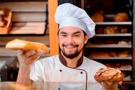 selling service smile: Only the best and fresh bakery. Cropped image of a handsome young man in a uniform holding two different loaves of bread  from the shop window in bakery shop