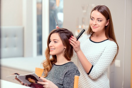 salon: Going for a change of style. Young beautiful woman discussing hairstyling with her hairdresser holding a comb and scissors while sitting in the hairdressing salon Stock Photo