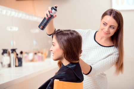 Getting ready for the runway. Side view of a young beautiful woman sitting in hair salon and looking into the mirror while her hairdresser getting her hair done with hair spray Stockfoto