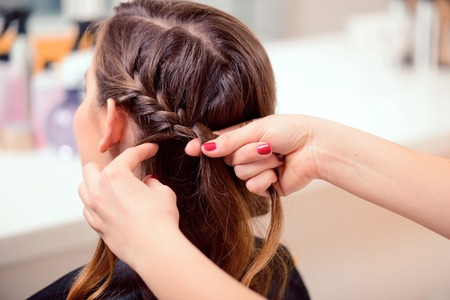 hairstyles: Super styling. Rear view closeup of a hairdresser braiding her clients hair in trendy weave plait while sitting in hairdressing salon