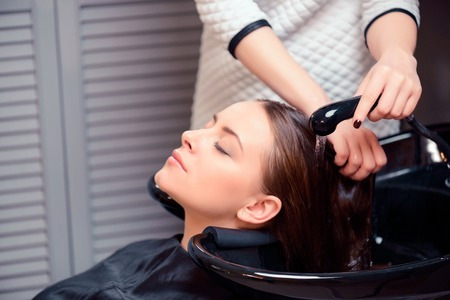 Was de stress weg. Bijgesneden shot van een jonge vrouw met haar haren wassen bij een professionele kapsalon