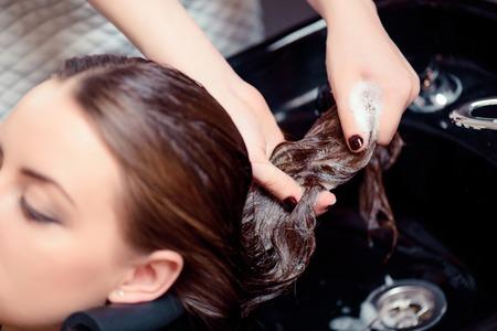 ストレスを洗い流します。プロのヘアケア サロンで洗浄彼女の髪を持つ若い女性のショットをトリミング
