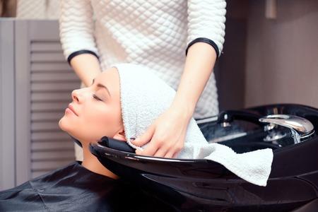 A boldogság a nap a szalonban. Közeli felvétel egy fiatal, mosolygós, nő a haját mosni és borított egy törülközőt egy professzionális fodrászat