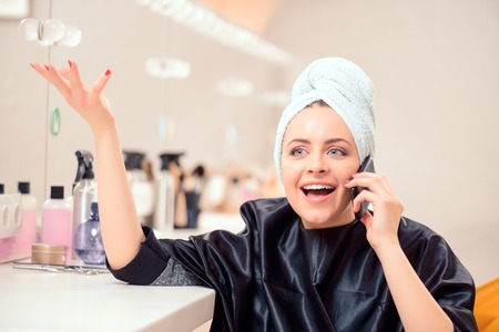 Taking care of business in the stylists chair. Beautiful emotional businesswoman talking over her mobile phone while sitting with a towel on her head at the hair salon photo