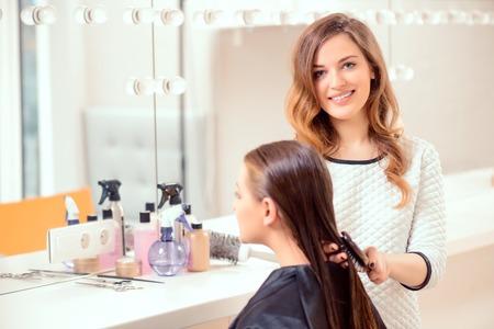 peluqueria: Me encanta mi trabajo. Peluquero hermoso que hace el peinado de su cliente y sonriendo a la cámara mientras está de pie en el fondo de un salón de peluquería profesional