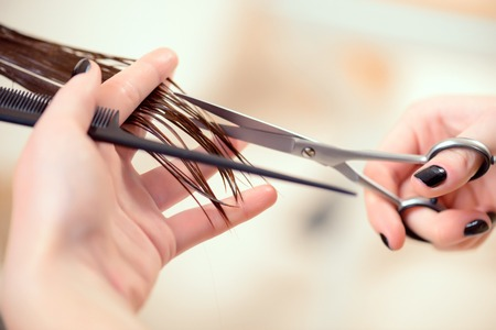 Getting rid of those split ends. Cropped shot of a female hairdresser cutting clients hair with scissors at beauty salon Stock Photo