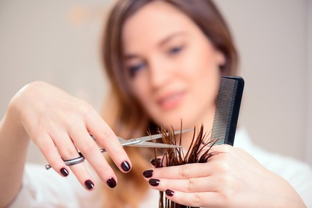 peluqueria: Voy a labrar su derecha. Imagen de enfoque selectivo de hermosa peluquería que hace el peinado con su cliente mientras está de pie en el fondo de un salón de peluquería profesional