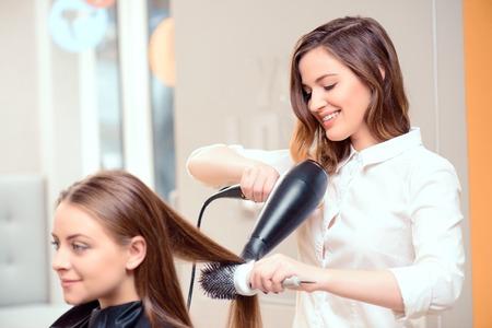 vẻ đẹp: Phong cách của các chuyên gia, bạn có thể tin tưởng. Gương phản ánh của một thợ làm tóc trẻ đẹp làm khách hàng mái tóc của mình với một mái tóc khô hơn trên nền của các salon làm tóc