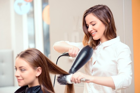 woman beauty: Stylish by professionals you can trust.  Mirror reflection of a young beautiful hairdresser doing her clients hair with a hair drier on the background of the hairdressing salon Stock Photo